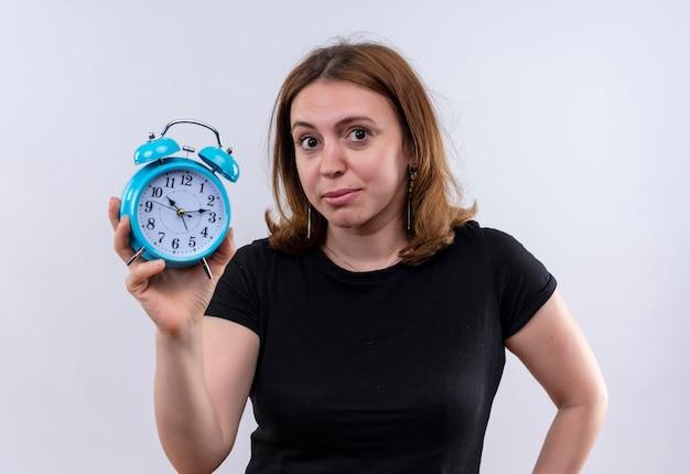 孤立した白い壁を見ている目覚まし時計を保持している若いカジュアルな女性