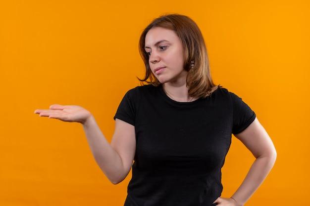 左側を見て、孤立したオレンジ色の壁に空の手を示す若いカジュアルな女性