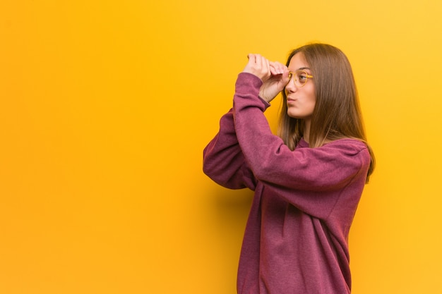 Young casual woman making the gesture of a spyglass