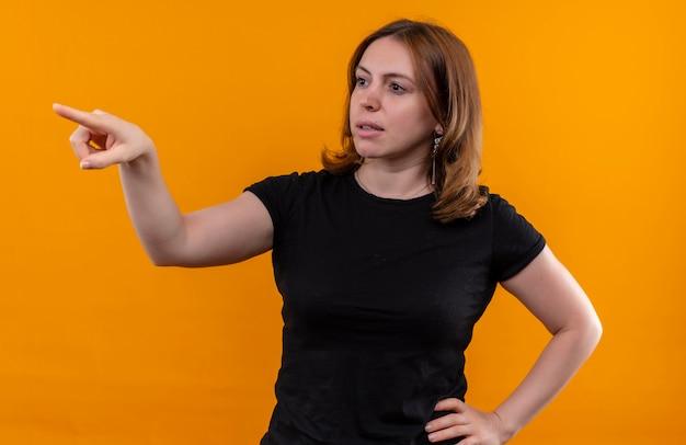 孤立したオレンジ色の壁に腰に手で左側を指して見て若いカジュアルな女性