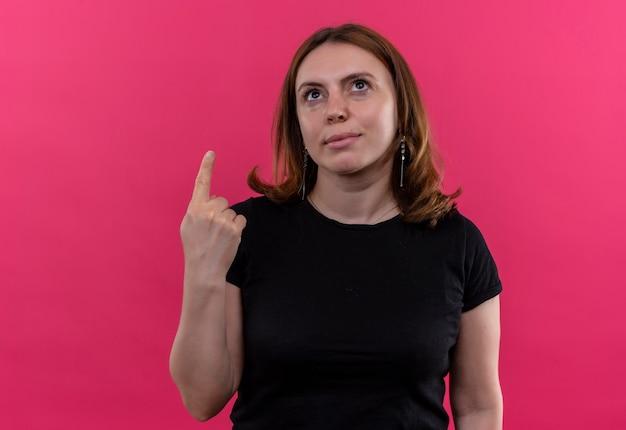 Giovane donna casuale che indica e che osserva in su sulla parete rosa isolata con lo spazio della copia