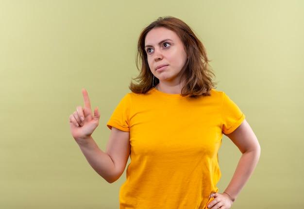 Giovane donna casual rivolta verso l'alto con la mano sulla vita sulla parete verde isolata con lo spazio della copia