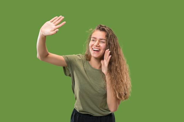 若いカジュアルな女性が叫んでいます。叫ぶ。緑のスタジオの背景で叫んで泣いている感情的な女性。女性の半分の長さの肖像画。