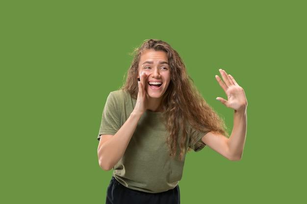 若いカジュアルな女性が叫んでいます。叫ぶ。緑のスタジオの背景に叫んで感情的な女性。女性の半身像。