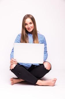 Giovane donna casuale che si siede sorridente che tiene il computer portatile isolato sul muro bianco
