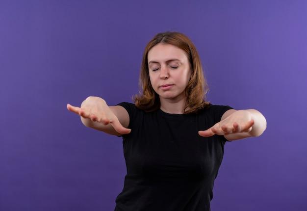 La giovane donna casuale che allunga distribuisce con gli occhi chiusi sulla parete viola isolata