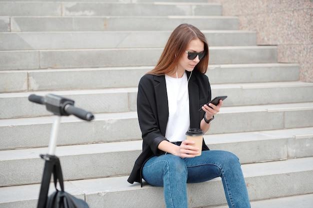 도시 환경에서 계단에 앉아 음악을 들으면서 스마트 폰에서 스크롤하는 긴 머리를 가진 젊은 캐주얼 여성