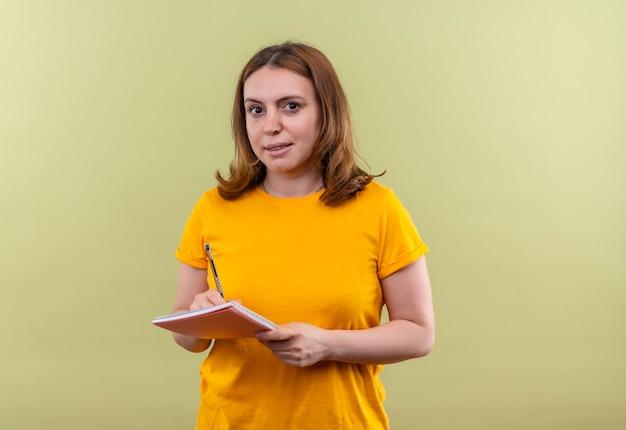 복사 공간이 격리 된 녹색 벽에 노트 패드에 뭔가 쓰는 젊은 캐주얼 여성