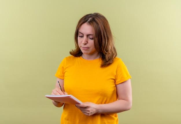 コピースペースと孤立した緑の壁のメモ帳に何かを書く若いカジュアルな女性