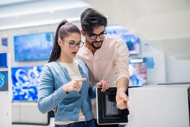 Молодая пара caucasain ищет микроволновую печь хорошего качества, стоя в магазине техники.