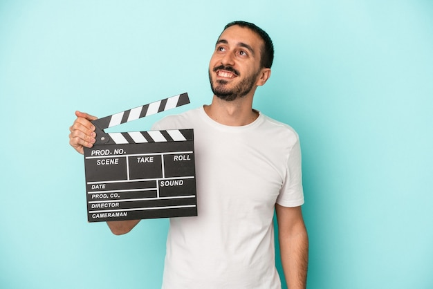 Young caucasian actor man holding clapperboard isolated on blue background dreaming of achieving goals and purposes