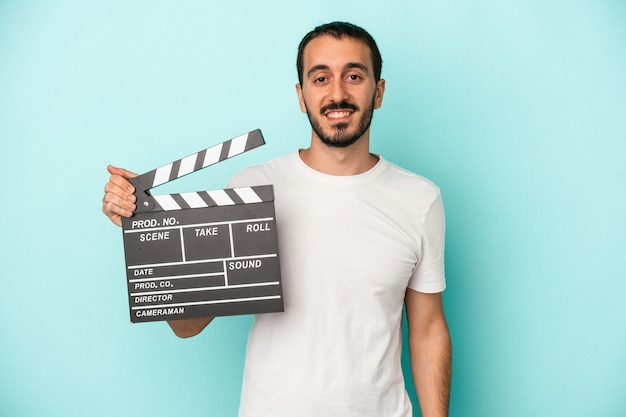 Young caucasian actor man holding clapperboard isolated on blue background happy, smiling and cheerful.