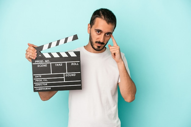Young caucasian actor man holding clapperboard isolated on blue background pointing temple with finger, thinking, focused on a task.