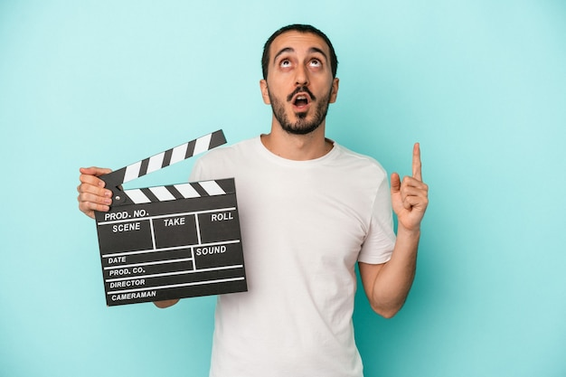 Young caucasian actor man holding clapperboard isolated on blue background pointing upside with opened mouth.