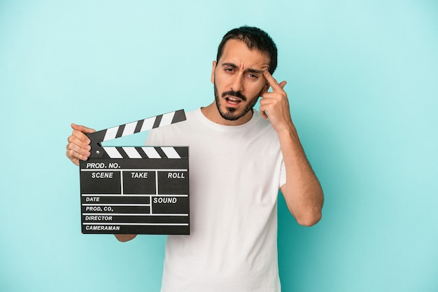 Young caucasian actor man holding clapperboard isolated on blue background showing a disappointment gesture with forefinger.