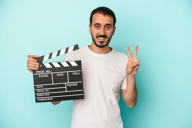 Young caucasian actor man holding clapperboard isolated on blue background showing number two with fingers.