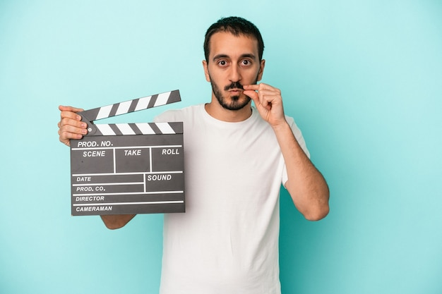 Young caucasian actor man holding clapperboard isolated on blue background with fingers on lips keeping a secret.