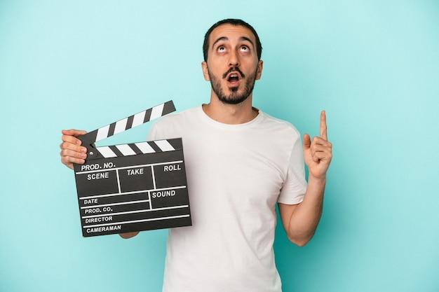 口を開けて逆さまを指している青い背景に分離されたカチンコを保持している若い白人俳優の男。