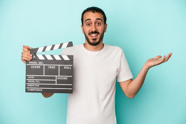 青い背景で隔離のカチンコを保持している若い白人俳優の男は、嬉しい驚きを受け取り、興奮し、手を上げます。