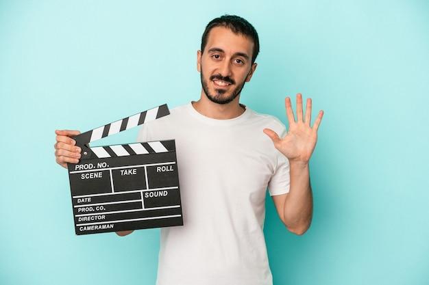 青い背景に分離されたカチンコを持っている若い白人俳優の男は、指で5番を示して陽気に笑っています。