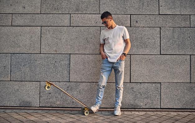 도시 건물의 벽에 롱보드가 달린 안경을 쓴 백인 젊은 남자