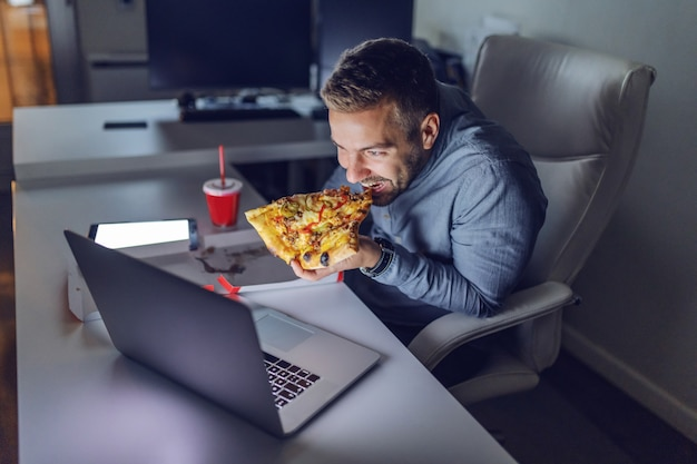 Young caucasian architect eating pizza at office.