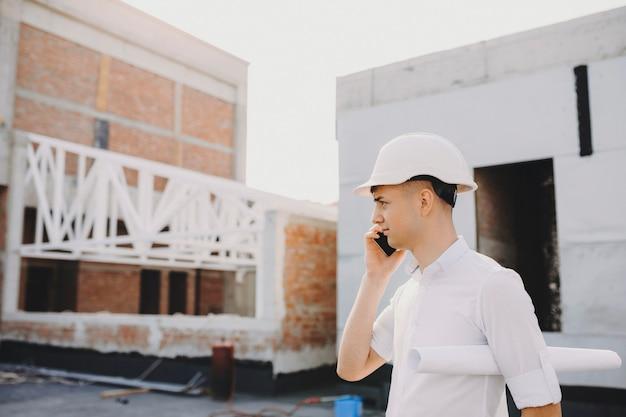 新しい建物の建設工事を視察しながらスマートフォンで話す若い白人建築家。