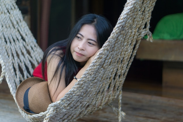 Young caucasian asian girl swinging in a hammock in a pleasant laziness of a weekend eveni
