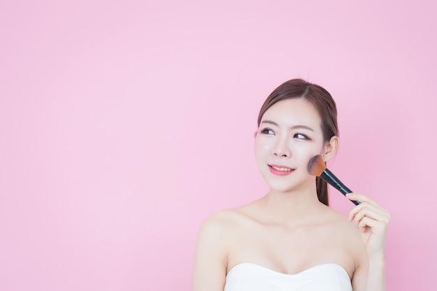 若い白人アジア人女性の笑顔はピンクの背景に化粧ブラシパウダーナチュラルメイクを適用します