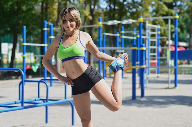 A young caucasian athlete girl in a bright green sportswear doing warm-up before training