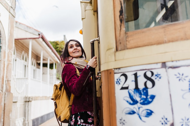 Young caucasian backpacker woman sightseeing porto views standing on a train. travel concept