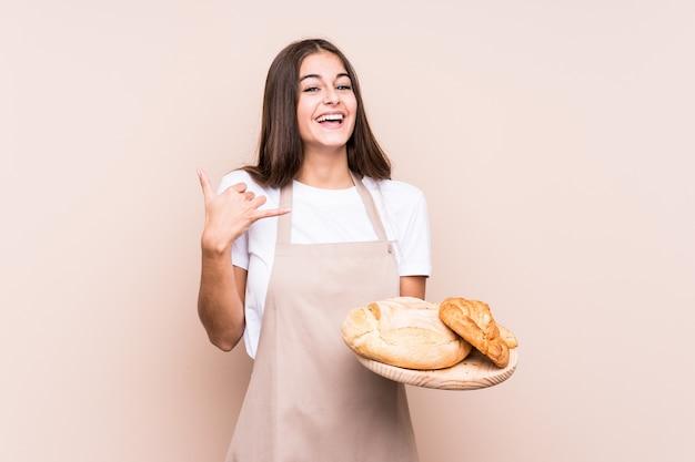 若い白人のパン屋の女性が指で携帯電話の呼び出しジェスチャーを示す分離しました。