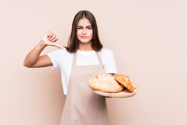 Young caucasian baker woman isolated showing a dislike gesture, thumbs down. disagreement concept.