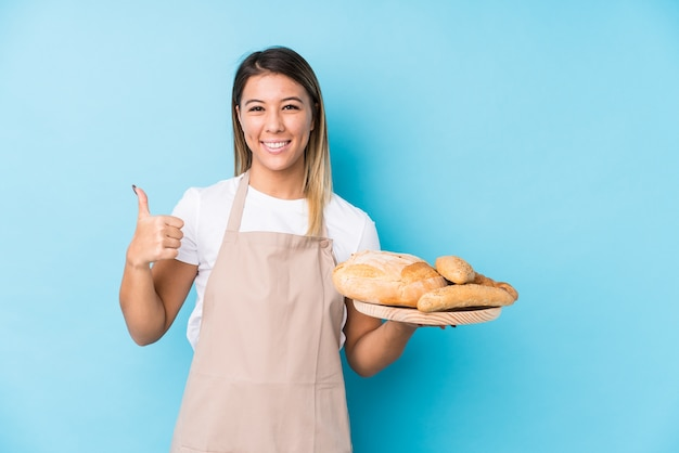 Young caucasian baker woman isolated smiling and raising thumb up