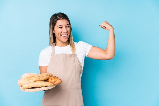 Young caucasian baker woman raising fist after a victory