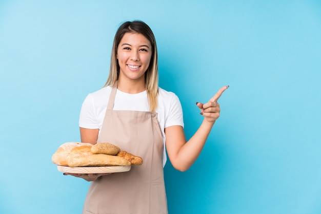 Young caucasian baker woman smiling and pointing aside, showing something at blank space.