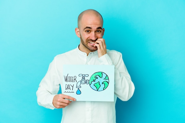 Young caucasian bald man celebrating world water day isolated on blue background biting fingernails