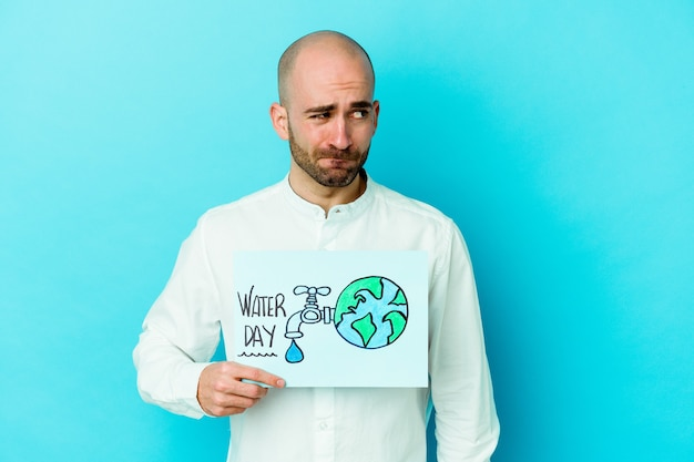 Young caucasian bald man celebrating world water day isolated on blue background confused