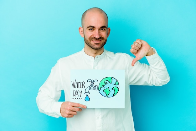 Young caucasian bald man celebrating world water day isolated on blue background showing a dislike gesture