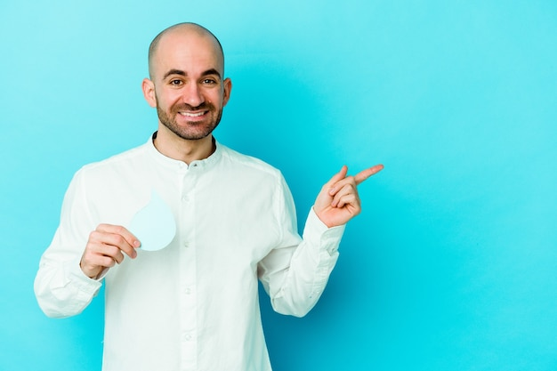Young caucasian bald man celebrating world water day isolated on blue background smiling and pointing aside