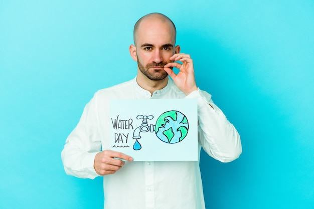 Young caucasian bald man celebrating world water day isolated on blue background with fingers on lips keeping a secret.