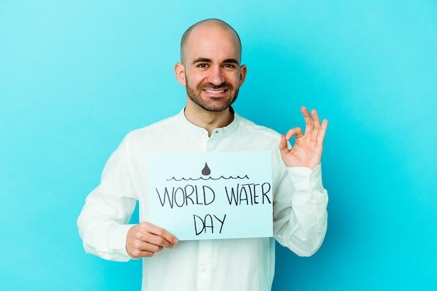 世界水の日を祝う若い白人のハゲ男は、青く陽気で自信を持って大丈夫なジェスチャーを示しています。