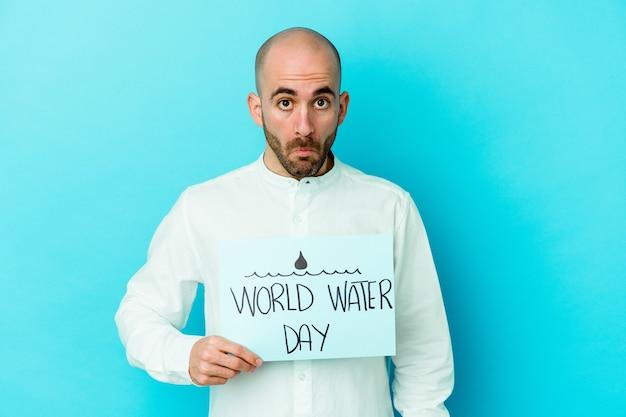 青い肩をすくめ、目を開けて孤立した世界水の日を祝う若い白人のハゲ男は混乱しました。