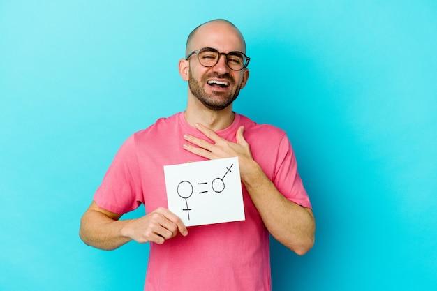 黄色の背景に分離された平等の性別のプラカードを持っている若い白人のハゲ男は、胸に手を置いて大声で笑います。