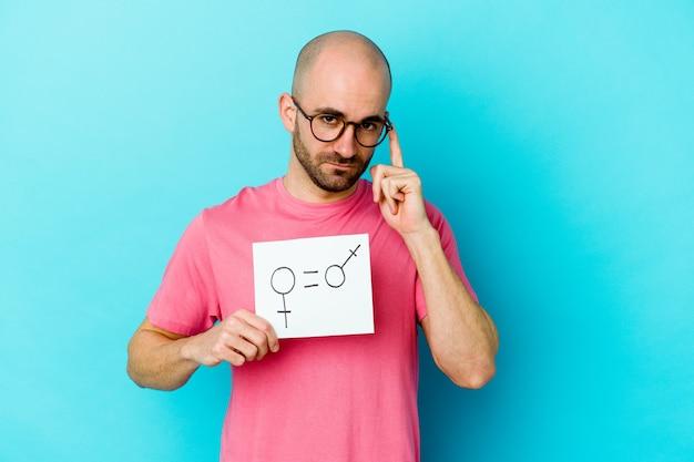 Молодой кавказский лысый мужчина держит плакат равенства полов, изолированные на желтом фоне, указывая висок пальцем, думая, сосредоточился на задаче.
