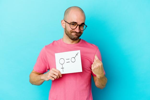 黄色い壁に隔離された平等な性別のプラカードを持っている若い白人のハゲ男が、誘うようにあなたに指を向けて近づいています。