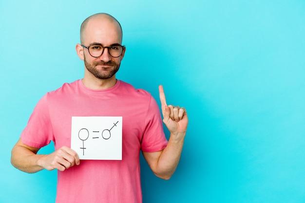 孤立した平等の性別プラカードを保持している若い白人ハゲ男