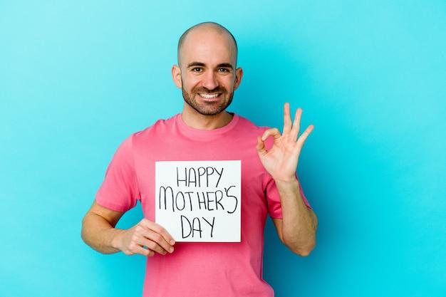 青の背景に分離された幸せな母の日のプラカードを持っている若い白人のハゲ男は、陽気で自信を持って大丈夫なジェスチャーを示しています。