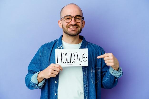 Молодой кавказский лысый мужчина держит праздничный плакат, изолированный на синем человеке, указывая рукой на пространство для копии рубашки, гордый и уверенный