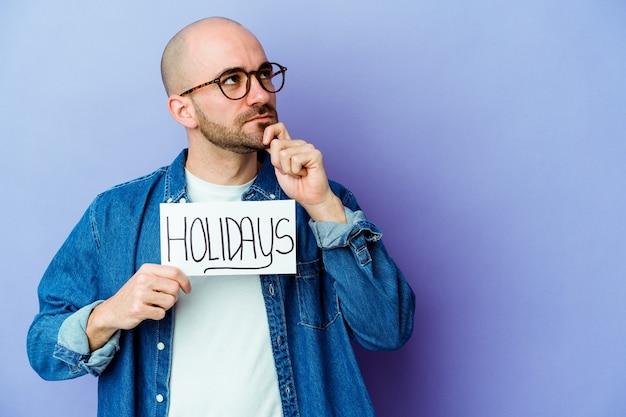 Молодой кавказский лысый мужчина держит праздничный плакат, изолированный на синей стене, смотрит в сторону с сомнительным и скептическим выражением лица.